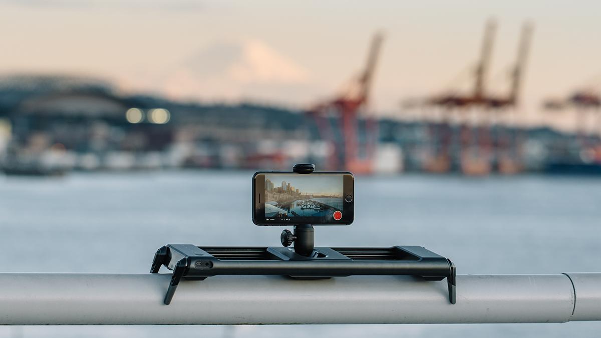 Slider med mobiltelefon monterad, i stadsmiljö